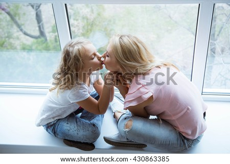 Mom and daughter blonde caucasians are sitting on a windowsill of a large window looking at each other. Beautiful smile. Happy beautiful family. Mothers Day - stock photo