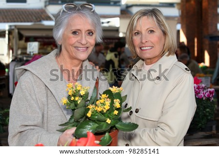 Mom and daughter buying flowers - stock photo
