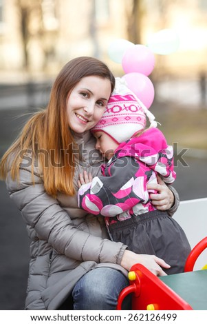 Mom and daughter cuddling on a park bench in spring day - stock photo