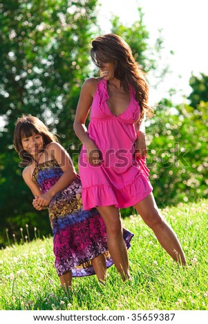 mom and daughter dancing and playing in a field - stock photo