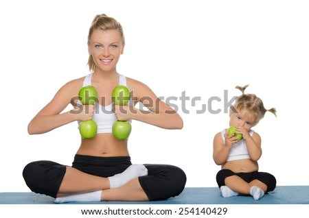 Mom and daughter engage in fitness dumbbells of green apples
