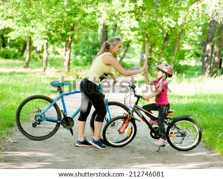 Mom and daughter give high five while cycling in the park  - stock photo