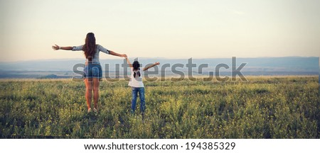 Mom and daughter go off into the distance on a beautiful meadow - stock photo