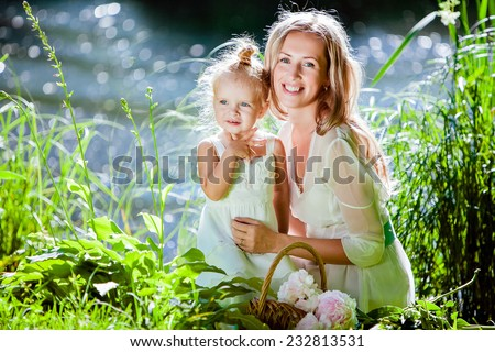 Mom and daughter happy smile on the background of the forest and water in backlight - stock photo