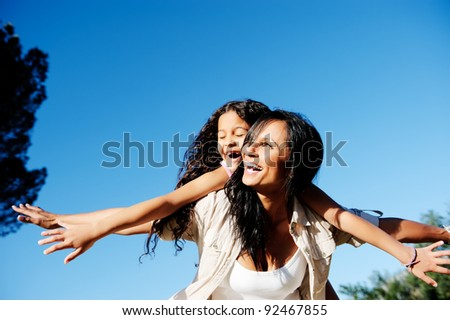 mom and daughter have fun outdoors, smiling and piggyback in the sunshine - stock photo