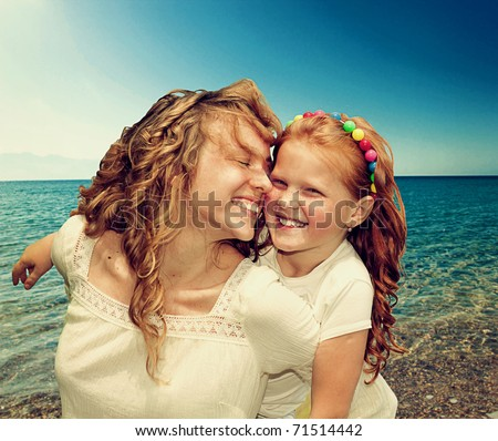 Mom and Daughter Having Fun against azure sea - stock photo
