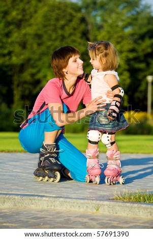Mom and daughter in roller skates - stock photo