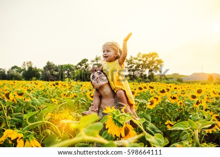 Mom and daughter in the field of sunflowers