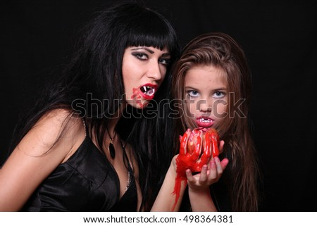 Mom and daughter in the image of vampires for Halloween