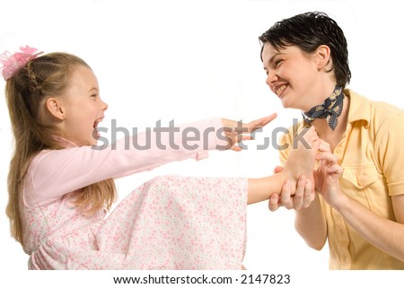 mom and daughter laughing while tickling feet - stock photo