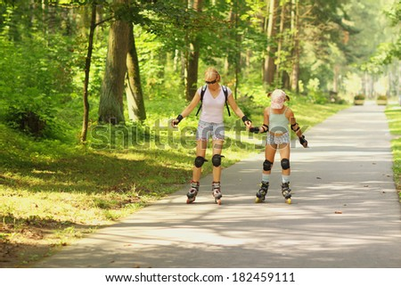 Mom and daughter learn to roller skate - stock photo