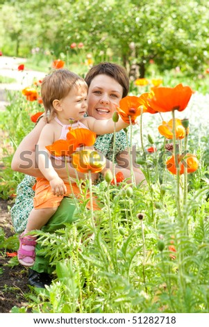Mom and daughter looking at poppy flowers - stock photo