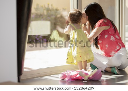 Mom and daughter looking through the window - stock photo