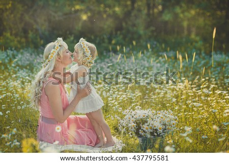 Mom and daughter on a picnic in the chamomile field. Two beautiful blondes in chamomile field on a background of horse. Mother and daughter embracing in the chamomile field - stock photo