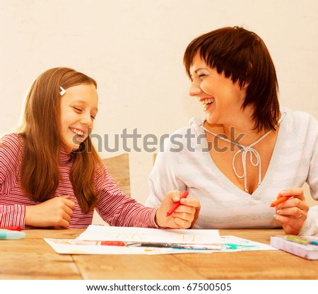 Mom and daughter painting on paper - family - stock photo