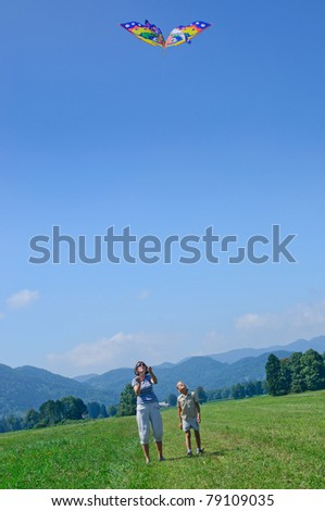 Mom and daughter play a kite in the Alps - stock photo
