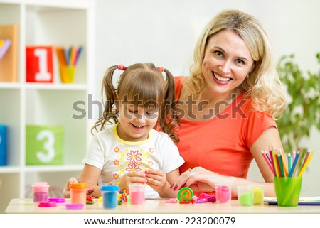 mom and daughter play colorful clay toy - stock photo
