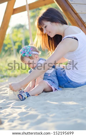 Mom and daughter play while sitting on the sand