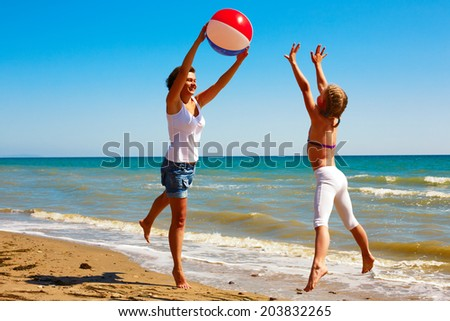 Mom and daughter play with a ball on the ocean shore on a sunny day in summer - stock photo