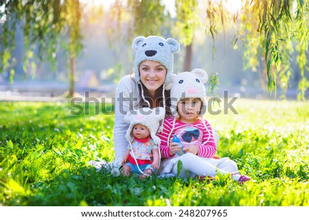 Mom and daughter playing in the park with a doll. - stock photo