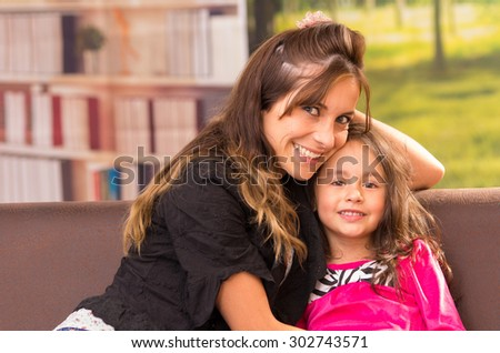Mom and daughter posing happily indoors having fun smiling to camera - stock photo