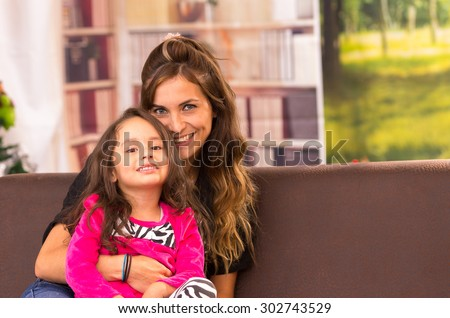 Mom and daughter posing happily indoors sitting in sofa with heads together smiling - stock photo