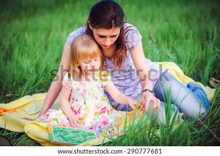 Mom and daughter reading a book in the park
