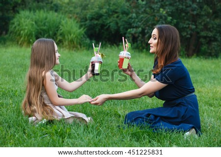 Mom and daughter resting in a park, the concept of family relations joy and happiness, advertising summer drinks - stock photo