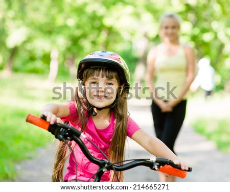 mom and daughter ride bikes in the forest