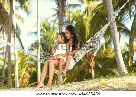 Mom and daughter sitting in a hammock by the sea enjoying nature and tropical palm trees, happy. Mothers day. - stock photo