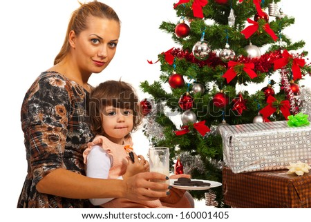 Mom and daughter sitting near Christmas tree with milk and biscuits - stock photo