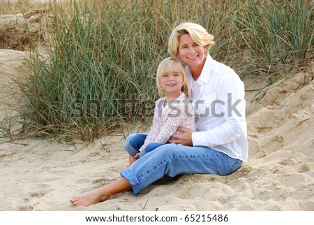 mom and daughter sitting on beach - stock photo