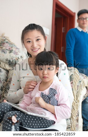 Mom and daughter sitting on the couch playing. - stock photo