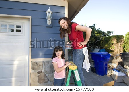 Mom and daughter smiling as they paint the house.. Horizontally framed photograph - stock photo
