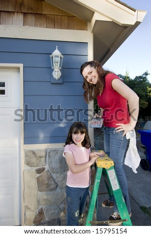Mom and daughter smiling as they paint the house. Vertically framed photograph - stock photo