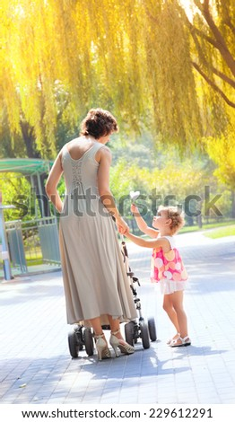 Mom and daughter walk in the rays of the autumn sun. - stock photo