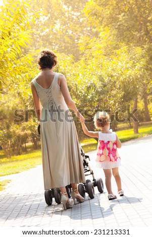 Mom and daughter walk in the rays of the autumn sun - stock photo