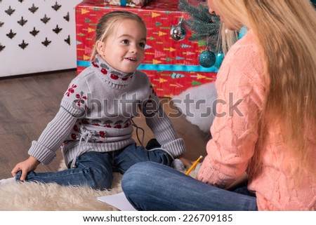 Mom and daughter wearing nice warm sweaters and jeans sitting aside on the floor near the Christmas tree talking and writing a letter for Santa - stock photo
