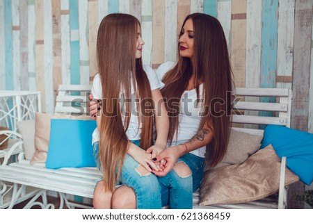 Mom and daughter with beautiful long hair and wearing the same clothes
