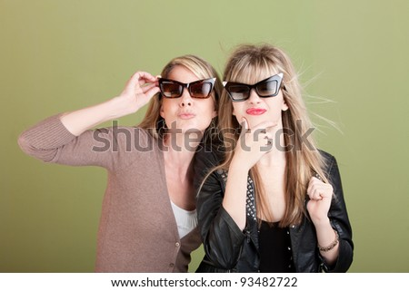 Mom and daughter with sunglasses over green background gaze - stock photo