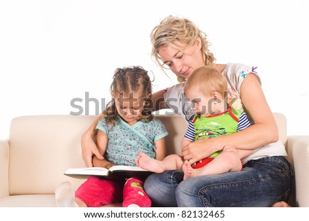 mom and her children reading at  sofa - stock photo