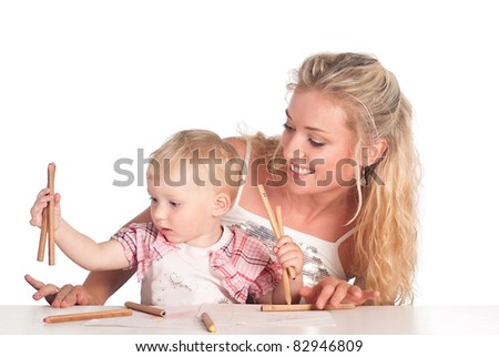 mom and her daughter drawing at table - stock photo