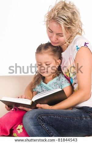 mom and her daughter read a book - stock photo