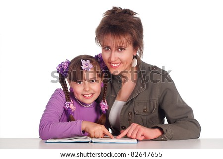 mom and her daughter reading a book - stock photo