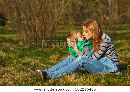 Mom and her son are sitting and hugging on the lawn in the autumn park. Family time. Happiness of childhood and motherhood. Outdoor Activities.