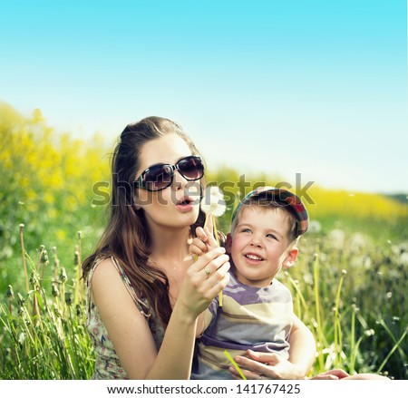 Mom and her son blowing off dandelion - stock photo