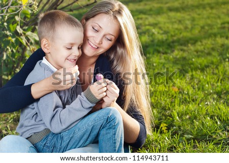 Mom and her son enjoyed the walk, sitting on the grass