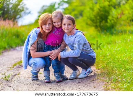 Mom and her two daughters in a summer park