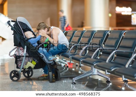 Mom and infant communicate while waiting for his flight at the airport on the chairs