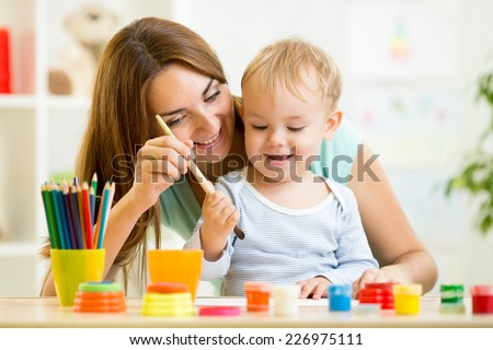 mom and kid boy painting together at home - stock photo
